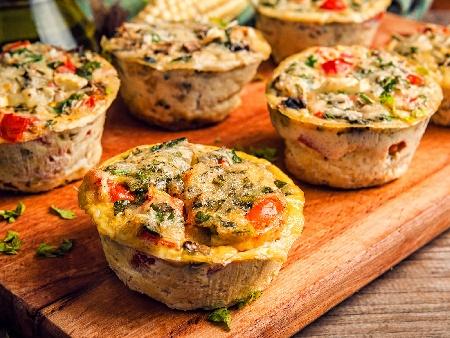 Печени мини омлети със зелен лук, сирене, чери домати и маслини във форма за мъфини на фурна - снимка на рецептата